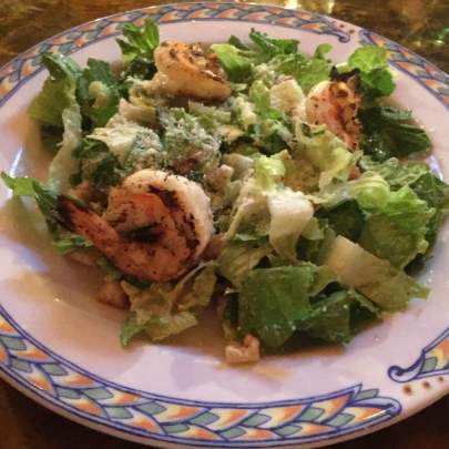 The ‎Caesar Salad with Grilled Shrimp from Di Mare Vero Beach starts with a base of fresh romaine lettuce, crunchy, baked in house croutons, parmesan cheese, lemon juice, extra virgin olive oil, egg, Worcestershire sauce, black pepper and is then topped off with three Grilled Jumbo Shrimp.